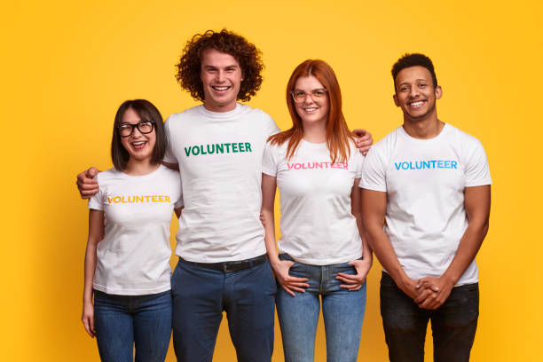 bénévoles multiethniques souriant pour l'appareil-photo - fond couleur uni photos et images de collection