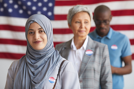 Multi-ethnic group of people at polling station on election day, focus on smiling Arab woman with I VOTED sticker looking at camera, copy space