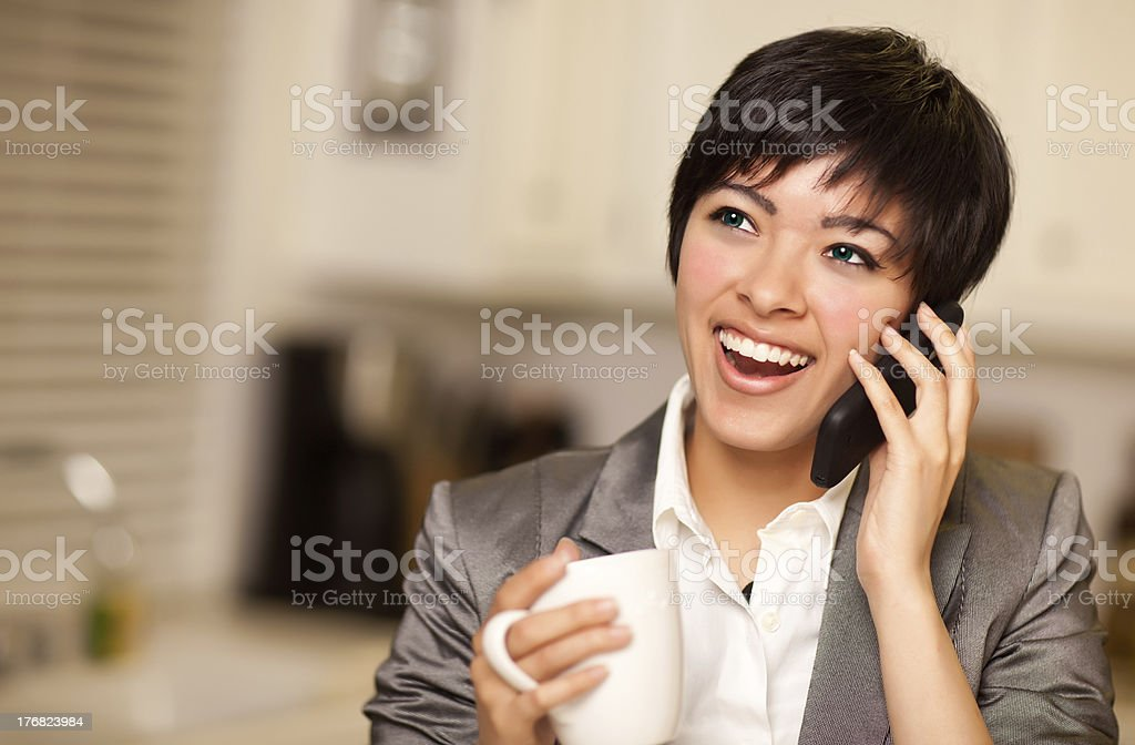 Multiethnic Woman with Coffee Talks on Cell Phone royalty-free stock photo