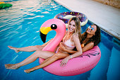 Young multi-ethnic women on summer holidays having fun floating on flamingo inflatable in swimming pool