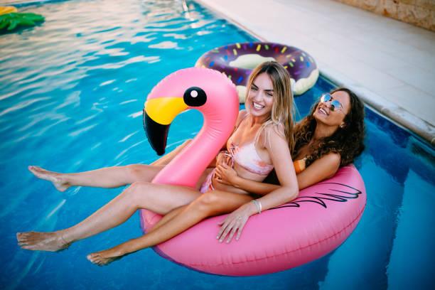 multietniska kvinnor ha kul flyter på flamingo uppblåsbara pool - inflatable ring bildbanksfoton och bilder