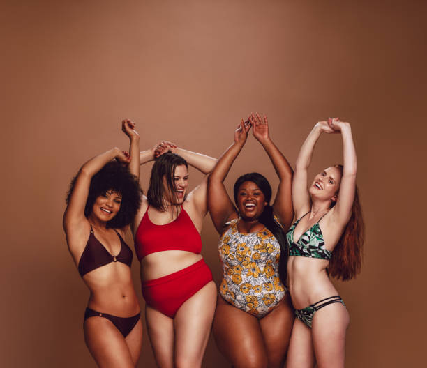Multi-ethnic women in swimwear enjoying themselves Group of different size women in bikinis dancing together. Multi-ethnic women in swimwear enjoying themselves in studio. body positive stock pictures, royalty-free photos & images