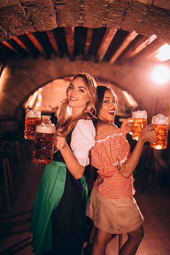 Multi-ethnic women in traditional German costumes drinking beer at Oktoberfest