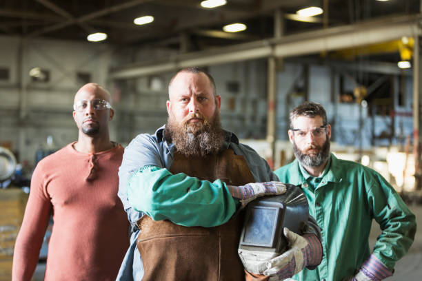 Multi-ethnic workers in metal fabrication plant stock photo