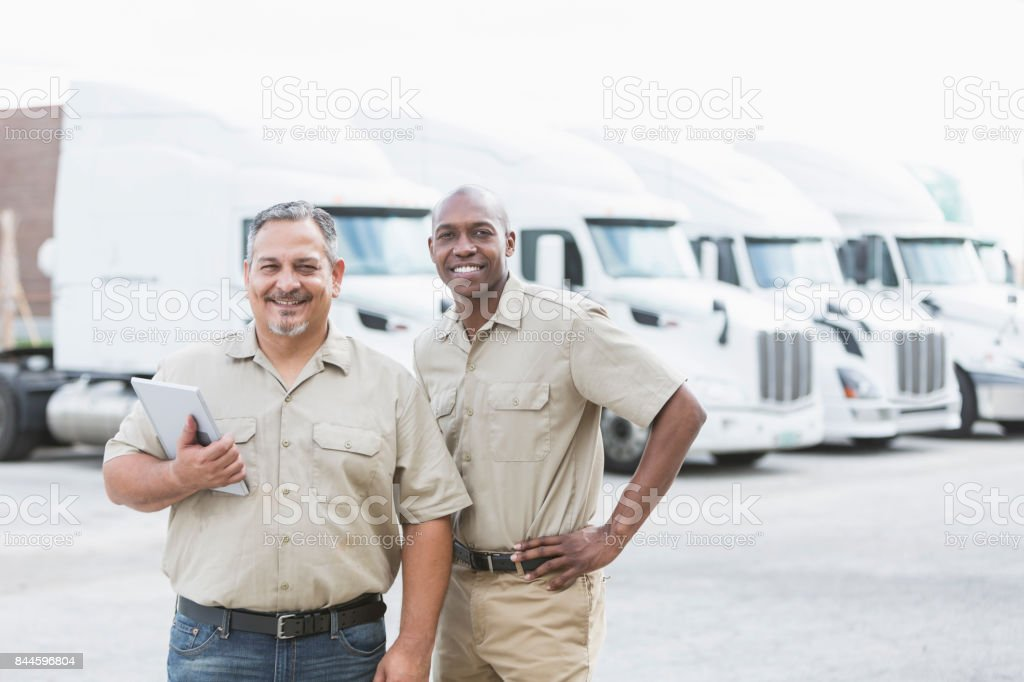 Multi-ethnic workers standing in front of semi-trucks stock photo
