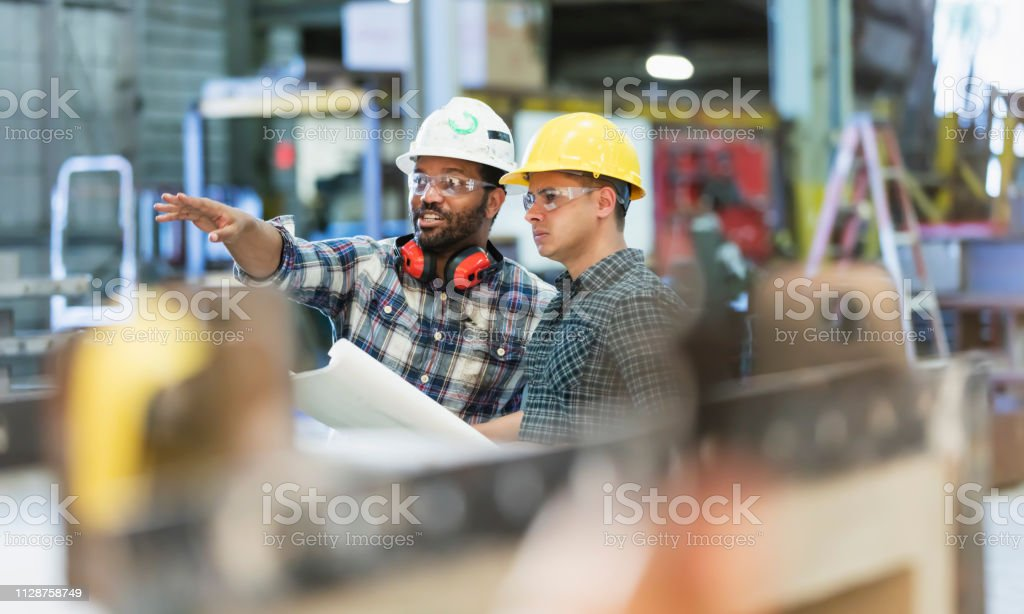 Multi-ethnic workers talking in metal fabrication plant Two multi-ethnic workers in their 30s talking in a metal fabrication plant wearing hardhats and protective eyewear. The man pointing is African-American and his coworker is Hispanic. 35-39 Years Stock Photo
