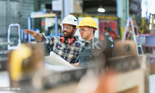 Two multi-ethnic workers in their 30s talking in a metal fabrication plant wearing hardhats and protective eyewear. The man pointing is African-American and his coworker is Hispanic.
