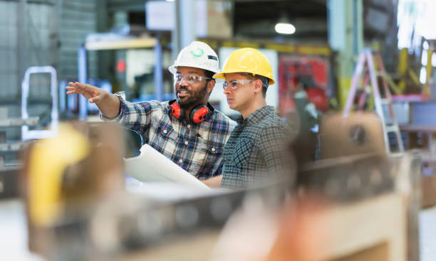 Multi-ethnic workers talking in metal fabrication plant Two multi-ethnic workers in their 30s talking in a metal fabrication plant wearing hardhats and protective eyewear. The man pointing is African-American and his coworker is Hispanic. manufacturing stock pictures, royalty-free photos & images