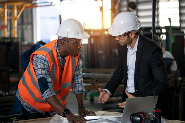 Multi-ethnic workers talking in metal fabrication plant stock photo