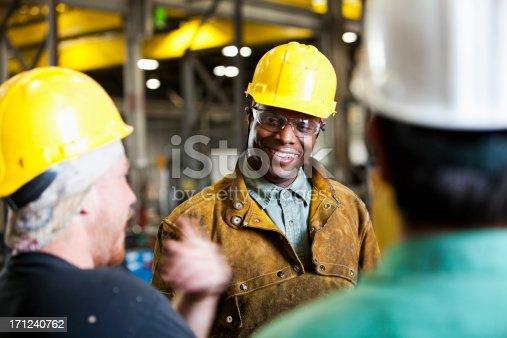 istock Multi-ethnic workers wearing hard hats, talking 171240762