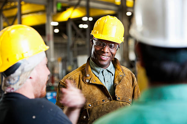 multi-ethnic workers wearing hard hats, talking - manufacturing occupation stock photos and pictures