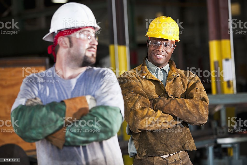 Multi-ethnic workers wearing hardhats royalty-free stock photo