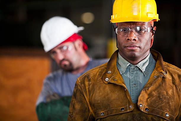 Multi-ethnic workers wearing hardhats stock photo