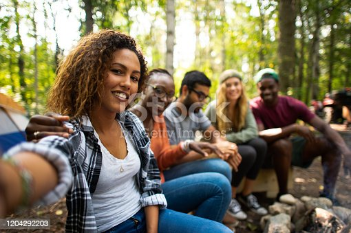 A group of multi-ethnic young adults sit on a wooden bench around a camp fire. They are all dressed casually in fall clothing and sitting around a fire pit.  The mixed race woman on the ed is holding out her camera to take a selfie of the group.