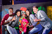 A group of four multi-ethnic teenagers and young adults having fun in a halloween haunted house, laughing, posing with a female zombie and scary dummy hanging from the wall.