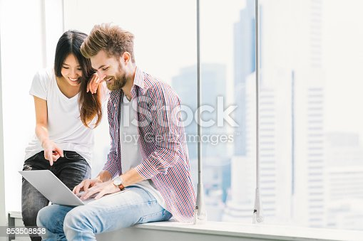 istock Multi-ethnic young couple or college student using notebook laptop together in campus or office. Information technology, education, startup business, or modern lifestyle concept. With copy space 853508858