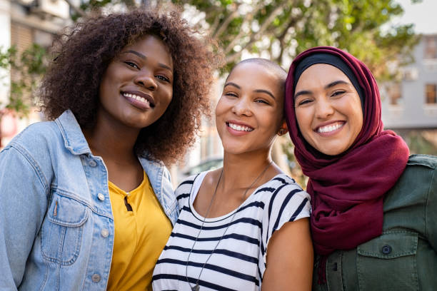 Multiethnic young friends enjoying together Group of three happy multiethnic friends looking at camera. Portrait of young women of different cultures enjoying vacation together. Smiling islamic girl with two african american friends outdoor. customs stock pictures, royalty-free photos & images