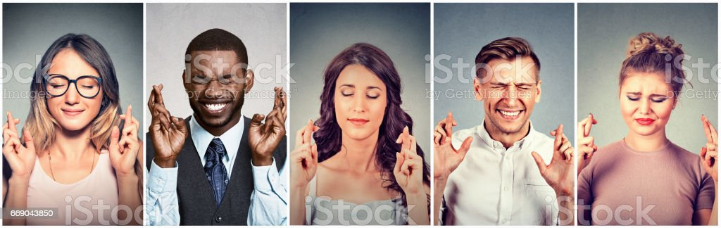 multiethnic young people hopeful crossing their fingers stock photo