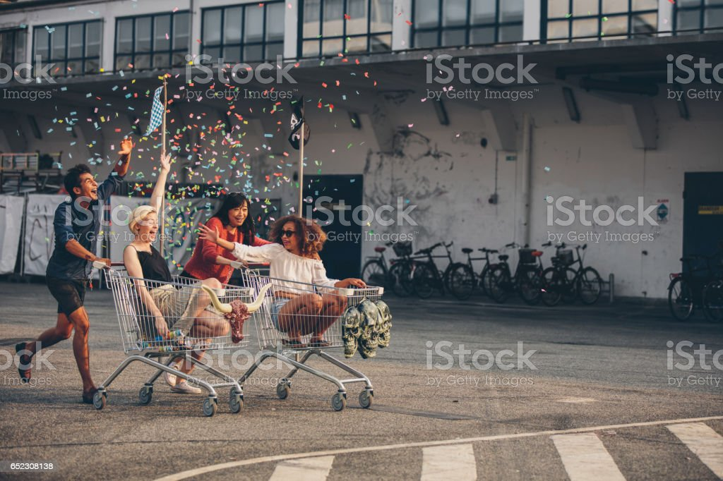 Multiethnic young people racing with shopping trolleys stock photo