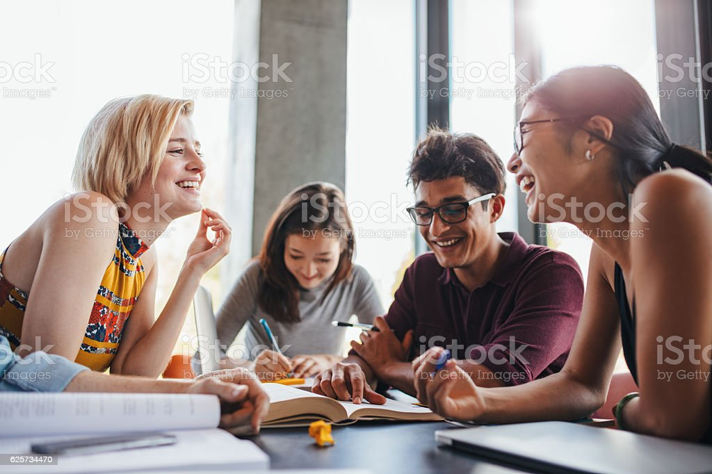 Multiethnic young people studying at school library stock photo