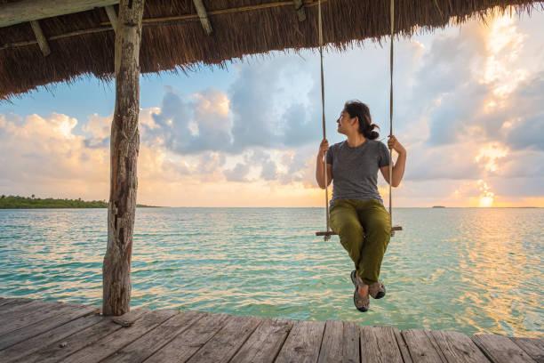 Multi-Ethnic Young Woman Sitting on Dock Swing Enjoying Ocean View stock photo