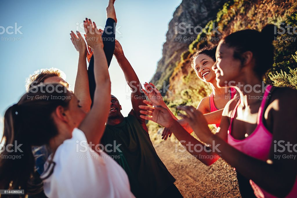 Multi-ethnical group of runners high fiving after a good run stock photo