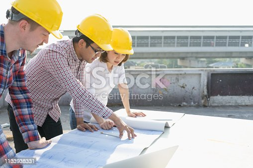 1047558948istockphoto Multiethnic,diverse group of young civil engineers,worker and architects discussing on drawing,blueprint construction with lowrise building background,wearing safety yellow helmet. Inspection concept. 1133938331