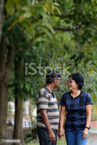 Married couple holding hands enjoying evening walk while having a good chat.