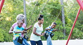 A multi-generation African-American family playing at the playground. The senior woman, in her 60s and her adult daughter, in her 30s, are pushing her two grandsons on swings. Mom is pushing the 4 year old boy and grandma is pushing her older, 5 year old grandchild.