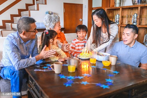 Multi-generation Chinese family celebrating child's birthday at home with traditional sponge cake and singing.