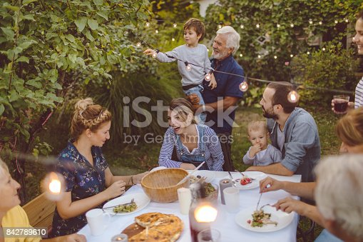 Photo of a multi-generation family having dinner outdoors in their back yard
