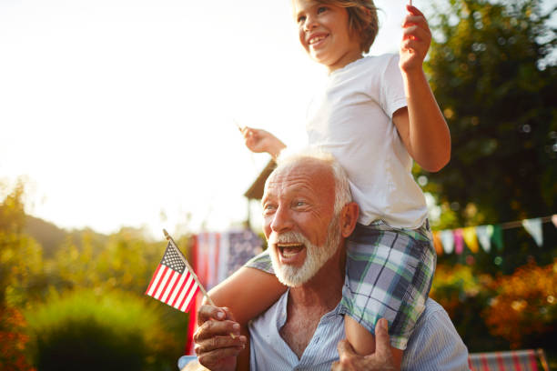 Multi-generation Family Celebrating 4th of July Multi-generation family on picnic in back yard celebrating 4th of July - Independence Day. Grandfather carrying grandson on shoulders. independence day photos stock pictures, royalty-free photos & images