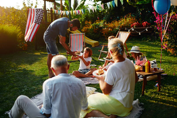 Multi-generation Family Celebrating 4th of July Multi-generation family on picnic in back yard sitting on blanket, eating burgers and celebrating 4th of July - Independence Day. family 4th of july photos stock pictures, royalty-free photos & images