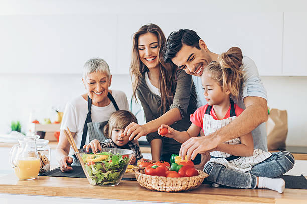 multi-generation family cooking - health and beauty stock photos and pictures
