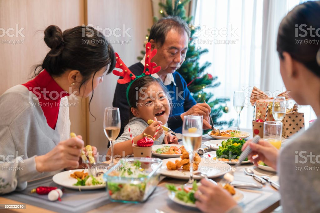 Multi-generation family eating Christmas dinner together stock photo
