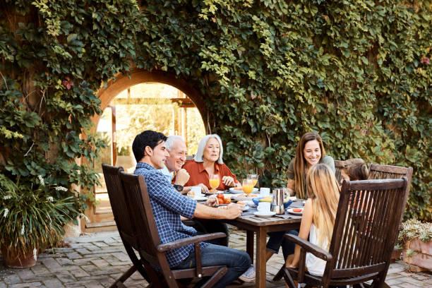 Mehrgenerationenfamilie beim Frühstück auf dem Hof – Foto