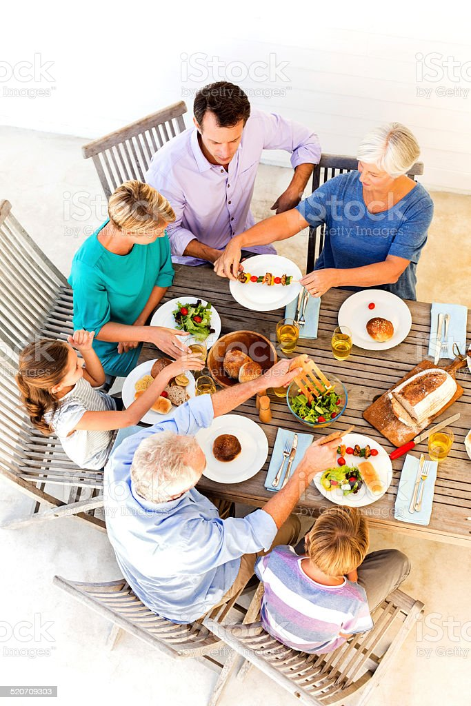 Multi-Generation Family Having Lunch Together Outdoor On Patio stock photo