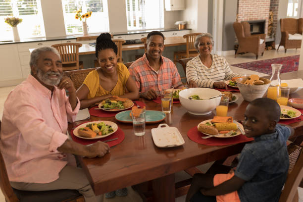 Multi-generation family having meal together on dining table at home stock photo