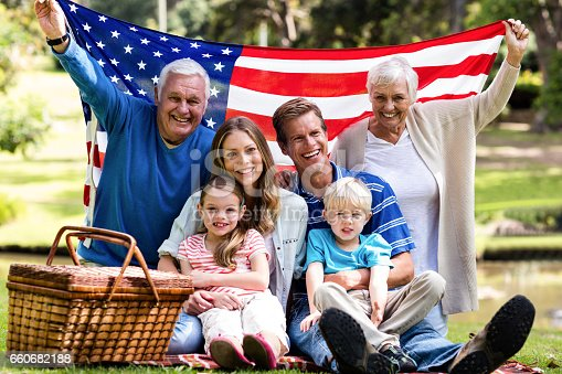 istock Multi-generation family holding american flag in the park 660682188