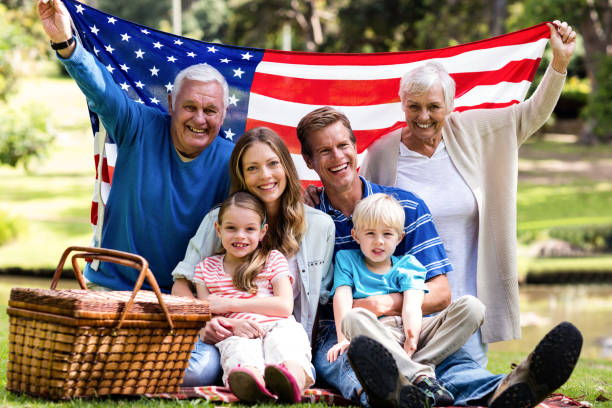 Multi-generation family holding american flag in the park stock photo