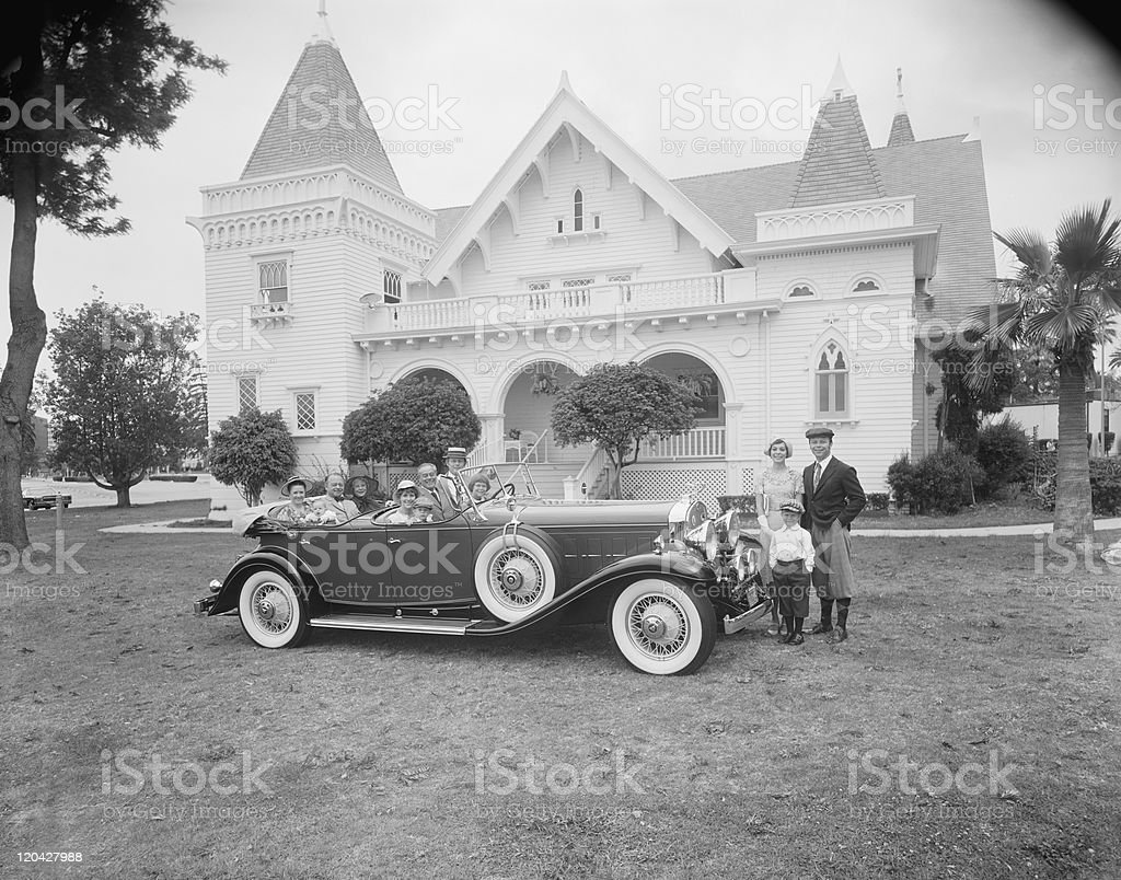Multigeneration family in car and outside car in front of house royalty-free stock photo
