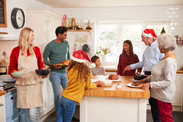multi-generation family in kitchen helping to prepare christmas meal together - christmas cooking imagens e fotografias de stock
