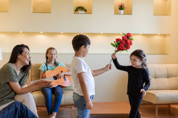 Multi-Generation Family is Enjoying in Birthday Party and is Listening to Guitar Playing by Young Girl. Cute Little Boy is Giving a Bouquet of Red Roses to his Young Sister. Family Members are Sitting on the sofa in the Living Room and Enjoy the Party. group of friends giving gifts to the birthday girl stock pictures, royalty-free photos & images