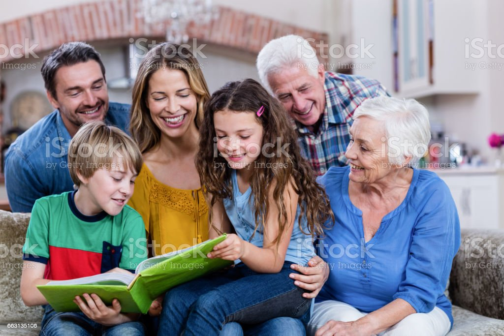 Multi-generation family looking at a photo album stock photo