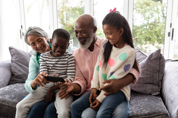 Multi-generation family looking at photos on mobile phone in living room stock photo