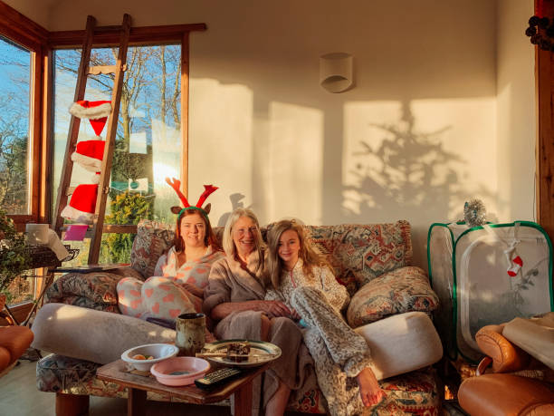 Multi-Generation Family on Christmas Day Two sisters are sitting on the sofa in the living room with their Grandmother on Christmas Day. They are wearing their pyjamas and costume reindeer antlers whilst smiling towards the camera. 12 17 months stock pictures, royalty-free photos & images