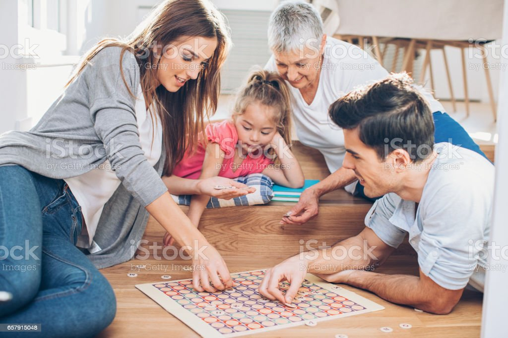 Multi-generation family playing a board game stock photo
