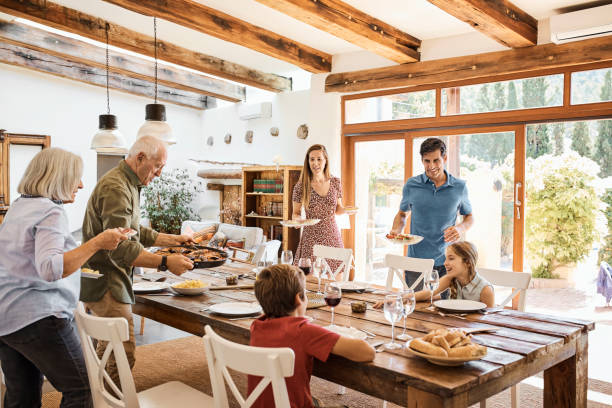 multi-generation family preparing for lunch at home - family gatherings stock pictures, royalty-free photos & images