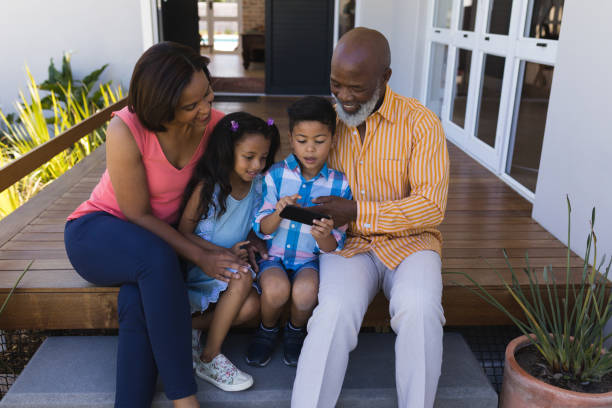 Multi-generation family reviewing photo on mobile phone on the porch stock photo