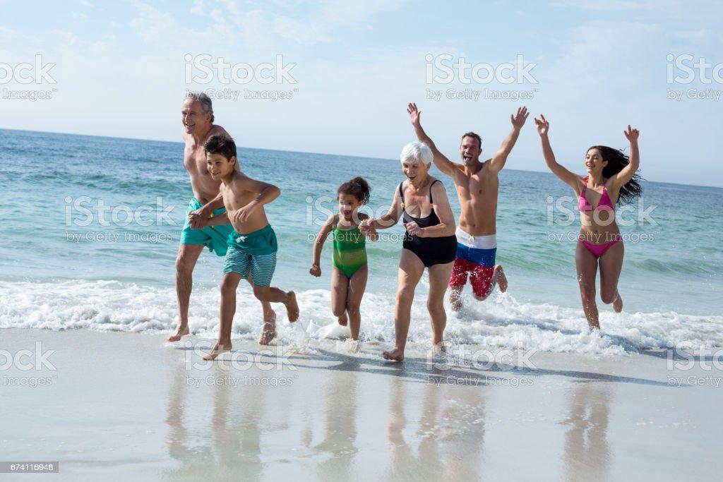 多代家庭中運行在海灘 免版稅 stock photo